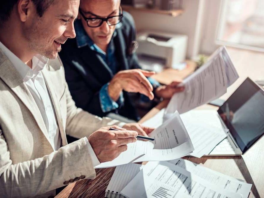 two business men reviewing financing paperwork